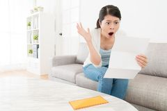 Attractive young female teenager sitting on sofa. Couch reading letter and getting bad news about company feeling shocked Stock Image