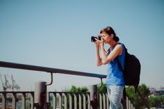 Attractive young female tourist with backpack and camera is exploring Hamburg city. Woman is making photo on retro royalty free stock photography