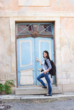 Attractive young female tourist opening door to a hostel Royalty Free Stock Photo