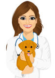 Attractive young female veterinarian hugging cute little dog Stock Photo