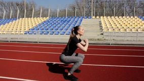 Attractive young fit active female athlete doing squats warm up stretch muscles outdoor working out outside big stadium stock footage