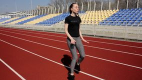 Attractive young fit active female athlete warm up stretch muscles outdoor working out outside big stadium on sunny day stock footage