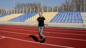 Attractive young fit active woman jumping with skipping rope working out warming up at big stadium on sunny spring day stock footage