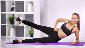 Attractive young fit female doing exercise on mat smiling having positive emotion