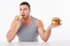 Attractive young fit guy chooses healthy food. Handsome man is holding hamburger and apple. He is biting fruit with pleasure. He did right choice. Isolated on royalty free stock images