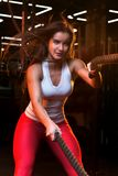 Attractive young fit pretty sportswoman is doing exercise with battle ropes stock image