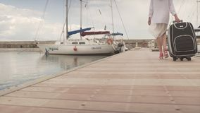 Attractive young fit woman in high heels turn back carrying heavy luggage walking on wooden bridge in yacht boat harbor. Young woman in high heels walking on stock footage