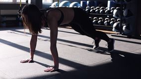 Attractive young fit woman wearing a black sports bra and leggings doing exercises on the floor in a gym. Outstretching stock footage