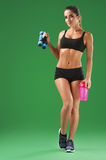 Attractive young fitness woman with a sports bottle on green bac Royalty Free Stock Photography