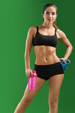 Attractive young fitness woman with a sports bottle on green bac Stock Image