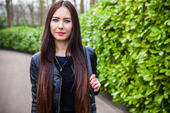 Attractive young friendly woman with long beautiful hairs posing in park Stock Images