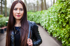 Attractive young friendly woman with long beautiful hairs posing in park Royalty Free Stock Photography