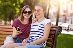 Attractive young friends sit in the park, discuss latest news in their lives. Adorable girls watch funny videos in net, read stock images