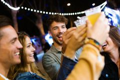 Attractive young friends toasting with beer in eat market in the street. royalty free stock photo