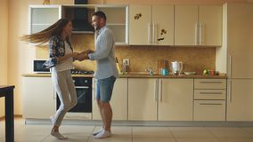 Attractive young funny couple have fun dancing while cooking in the kitchen at home Royalty Free Stock Photos