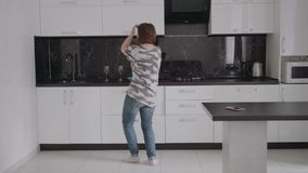 Attractive young funny woman dancing and singing in kitchen at home stock footage
