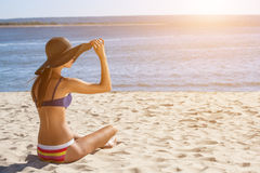 Attractive, young girl in a bathing suit sitting on the beach and sunbathing Stock Images
