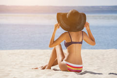 Attractive, young girl in a bathing suit sitting on the beach and sunbathing on the sunset sky Royalty Free Stock Image