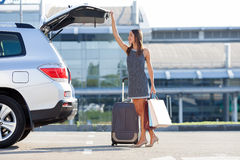 Attractive young girl is beginning her journey. Cheerful woman is standing near her car and closing the trunk. She is holding many packets of bought things and Royalty Free Stock Photo