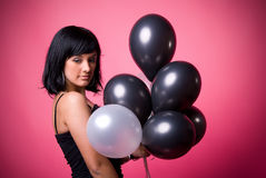 Attractive young girl with birthday balloons. Photo of a young girl with a black and white balloons on a pink background Stock Photography