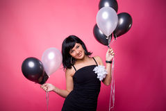 Attractive young girl with birthday balloons. Photo of a young girl with a black and white balloons on a pink background Stock Images