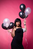 Attractive young girl with birthday balloons. Photo of a young girl with a black and white balloons on a pink background Royalty Free Stock Photography
