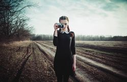Attractive young girl in black dress taking pictures by classic film camera. Outdoor portrait in the field stock photos