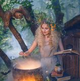 Attractive young girl with blond hair with an amazing lush wreath on her head in the forest, preparing potion in cauldro stock photo