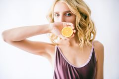 Attractive young girl with blond hair in a bikini and lemon halves royalty free stock photo