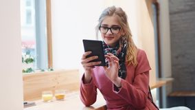 Attractive young girl in a breakfast café, using her tablet, touches her glasses and smiling to herself. Stylish outfit stock video footage