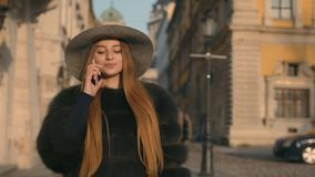 Young girl calling somebody on the phone, talking and smiling happily. Attractive young girl calling somebody on the phone, then gladly talking and smiling stock video footage