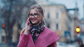 Attractive young girl calling somebody on the phone, then gladly talking and smiling happily. Stylish look, pink cozy. Coat, casual accessories. Trendy look stock video