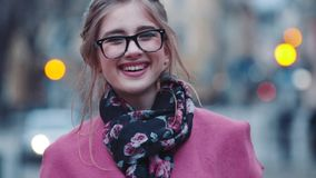Attractive young girl with casual haircut holding a cup of hot coffee and using her cell phone for texting, then looks. Right in the camera and smiles happily stock video footage