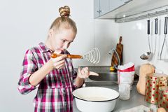 Attractive young girl is cooking on kitchen. Making cakes and cookies. stock photo