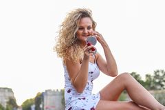 Attractive Young Girl With Curly Blonde Hair Checking Her Make U. P Looking at Small Pocket Mirror Royalty Free Stock Images