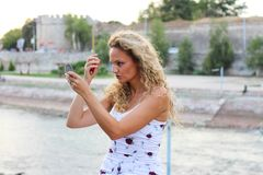 Attractive Young Girl With Curly Blonde Hair Checking Her Make U. P Looking at Small Pocket Mirror Stock Photography