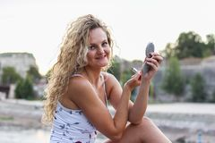 Attractive Young Girl With Curly Blonde Hair Looking at the Came. Ra and Holding a Red Lipstick and a Small Pocket Mirror Royalty Free Stock Image