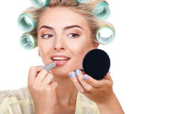 Attractive young girl is doing make-up and Royalty Free Stock Images