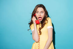 Attractive young girl in dress talking on retro telephone tube Royalty Free Stock Images