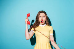 Attractive young girl in dress talking on retro telephone tube Stock Photos