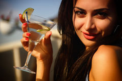 Attractive young girl drinking martini. Attractive young girl holding a glass and drinking martini cocktail Stock Image
