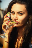 Attractive young girl drinking martini. Attractive young girl holding a glass and drinking martini cocktail Stock Photos