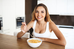 Attractive young girl eating cornflakes with milk looking at camera smiling Royalty Free Stock Photography