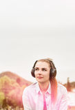 Attractive young girl enjoying music in a sunny day outside Royalty Free Stock Photography