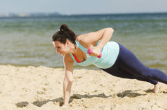Attractive young girl exercising with dumbbells on a beach in the summer Royalty Free Stock Images