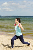 Attractive young girl exercising with dumbbells on a beach in the summer Stock Images