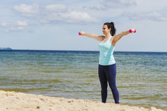 Attractive young girl exercising with dumbbells on a beach in the summer Stock Photos