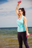 Attractive young girl exercising with dumbbells on a beach in the summer Stock Photography