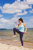 Attractive young girl exercising with dumbbells on a beach in the summer Royalty Free Stock Photo