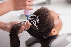 Attractive young girl is getting a hairwash in. Beautiful woman is having her hair washed in beauty shop. She is sitting with joy and relaxing. The hairdresser Royalty Free Stock Images